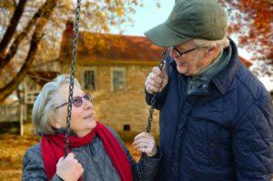 Starsza kobieta nahuśtawce, mężczyzna koło niej – cieszą się wspólną rozmową