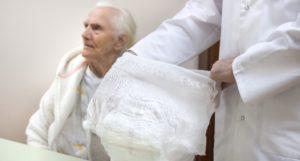 Opiekun pacjenta trzymający pieluchomajtki ipacjent wtle