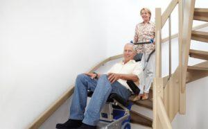 Osoba poruszająca się naschodołazie zpomocą opiekuna