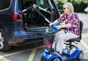 Aktywny senior naskuterze elektrycznym pakuje zakupy doauta