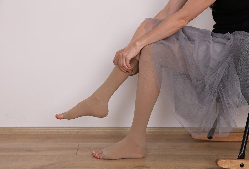 Kobieta zakłada pończochy uciskowe przeciw żylakom - brandvital.eu