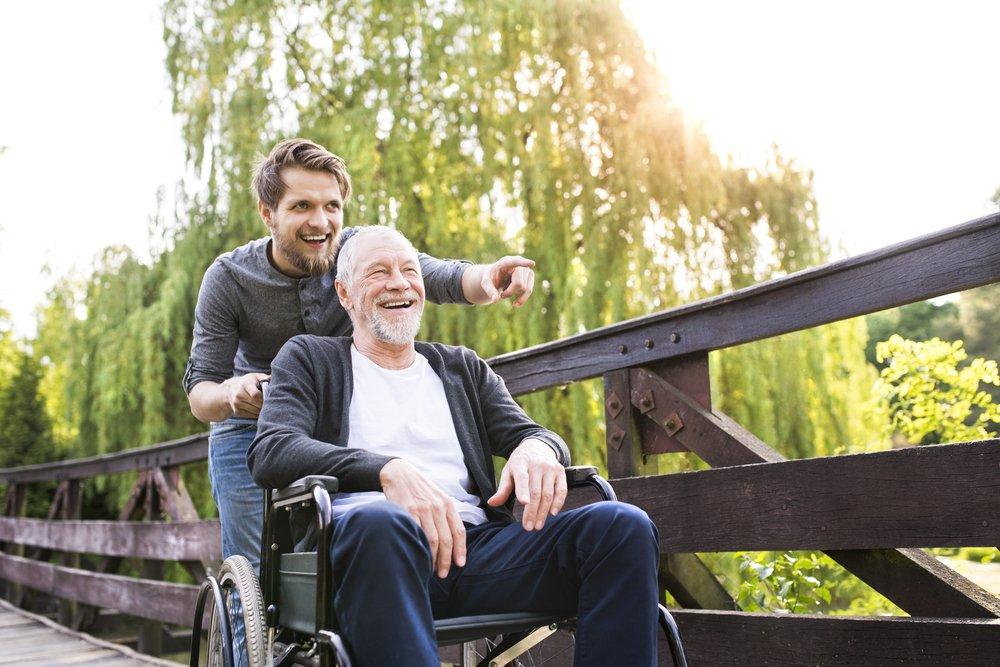 Ojciec naspacerze zsynem korzystający zwypożyczonego wózka inwalidzkiego - brandvital.eu