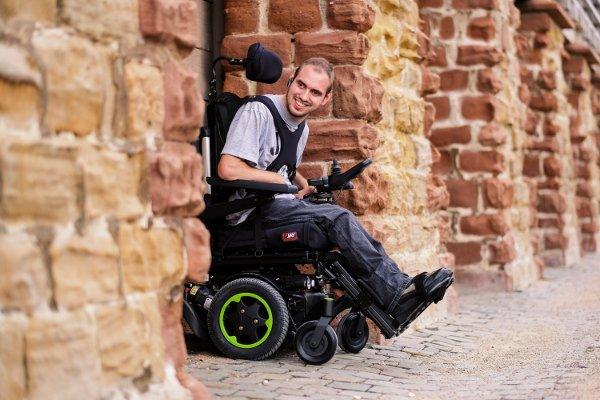 Mężczyzna naelektrycznym wózku inwalidzkim samodzielnie przemierza miasto