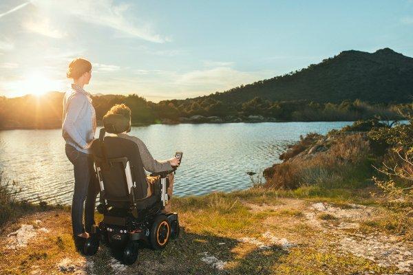 Mężczyzna nawózku inwalidzkim elektrycznym patrzący najezioro. Obok stoi kobieta