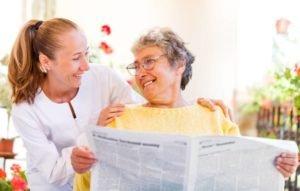 starsza kobieta nafotelu geriatrycznym zopiekunką