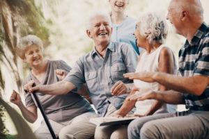 Seniorzy siedzą naławce irozmawiają. Takmożna testować aparaty słuchowe powizycie uprotetyka słuchu.
