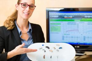protetyk słuchu pokazuje modele aparatów słuchowych