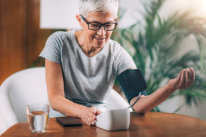 Kobieta mierząca ciśnienie zapomocą ciśnieniomierza naramiennego