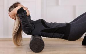 kobieta używająca rollera aby załagodzić ból pleców ikręgosłupa
